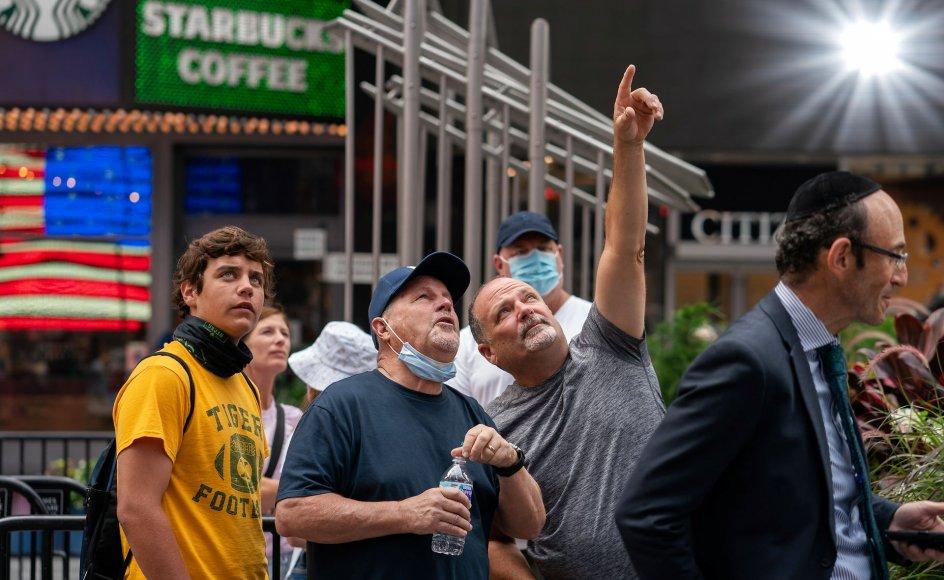 En gruppe mennesker følger milliardæren Jeff Bezos rumrejse på en skærm på Times Square i New York.