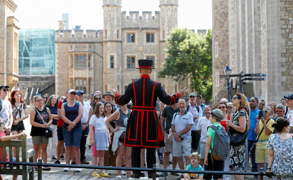På frihedsdagen var fremmødet også stort ved turistattraktioner som Tower of London, hvor Yeoman-vagten Barney Chandler her taler til det første hold uden mundbind, der deltager i den første Beefeater-rundtur i 16 måneder. – Foto: Peter Nicholls/Reuters/Ritzau Scanpix.