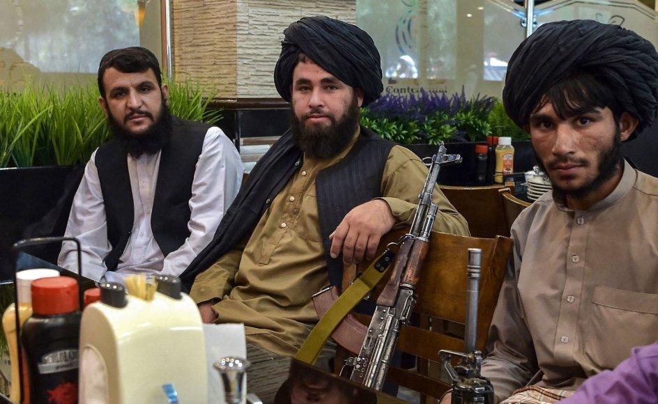 Taleban-krigere har taget deres rifler med til bords på en restaurant i Kabul den 26. august, mens de venter på, at maden bliver serveret.