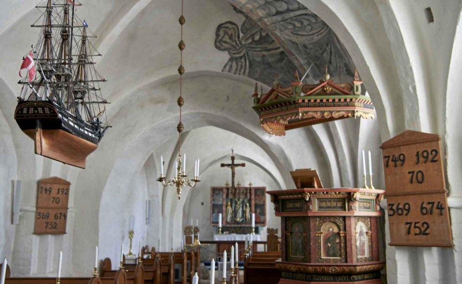"""Som barn kom Samuel Nymann Eriksen i en kirke, hvor et skib hang fra loftet som symbol på menighedens sejlads mod himlen. Jesus lovede ikke kun sejlruter i rolige, demokratiske farvande, men også ind i diktaturstater med bølgegang og storm. Men også her er det kirkens opgave at kaste redningskranse til mennesker i åndelig havsnød, skriver han. På billedet ses kirkeskibet i Tunø Kirke, en model af linjeskibet """"Louise Augusta"""", søsat 1783. – Foto: Morten Rasmussen/Biofoto/ Ritzau Sc"""