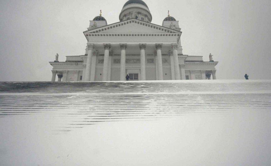 Normalt er Helsinki Domkirke, der blev opført i perioden mellem 1830 og 1852, ikke lige til at overse i den finske hovedstad. Men når snestormen rammer, bliver risikoen lidt større. Den 12. januar var det i hvert fald svært at skimte de i alt 43 trappetrin, der leder op til Storkirken, som den også kaldes. – Foto: Vesa Moilanen/AFP/Ritzau Scanpix.