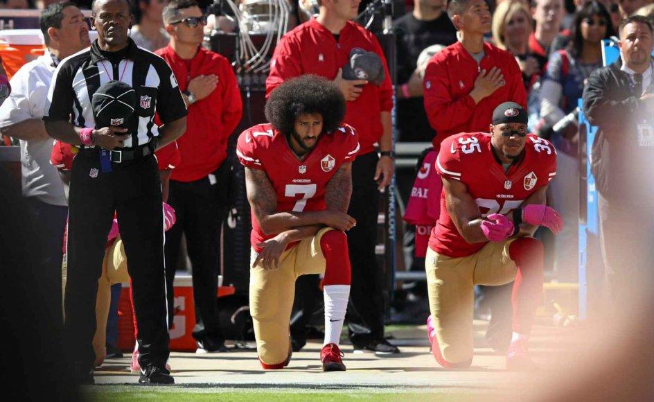 Den tidligere quarterback i den amerikanske fodboldliga NFL Colin Kaepernick (tv.) tog initiativ til at knæle imod racisme forud for kampe. Bevægelsen har bredt sig til sportsstjerner over hele verden. Holdkammeraten Eric Reid var en af de første til at tage del i aktionen som her under en kamp i oktober 2016, men fik aldrig samme kontroversielle status i den brede offentlighed. – Foto: Ezra Shaw/AFP/Ritzau Scanpix.