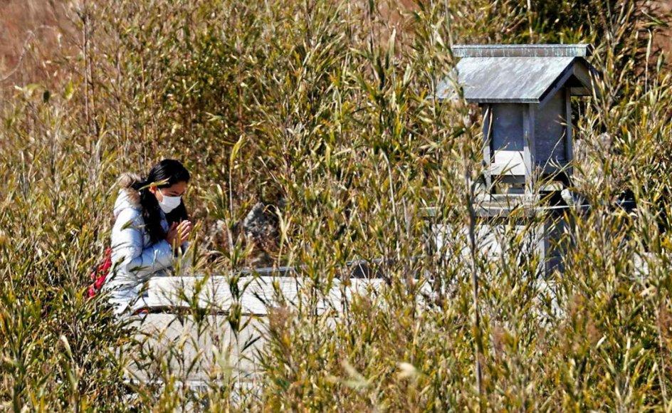 2En kvinde ses her i søndags bede en stille bøn ved et mindesmærke for nogle af de knap 20.000 ofre for tsunamien for 10 år siden. I baggrunden skimtes et væld af sorte plasticsække med radioaktiv jord, og det er især frygten for radioaktivitet, der har sat dybe spor i mange japaneres sind. – Foto: Kyodo/AP/Ritzau Scanpix.
