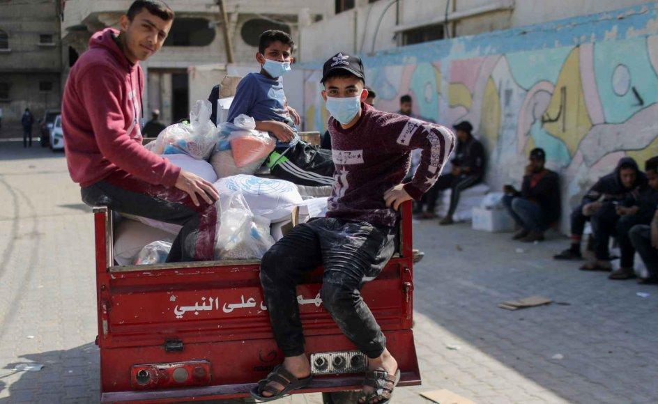 Palæstinensiske drenge ses her med madforsyninger, som de har fået af FN's hjælpeorganisation for palæstinensiske flygtninge i Mellemøsten (UNRWA) onsdag i flygtningelejren Beach i Gaza City.