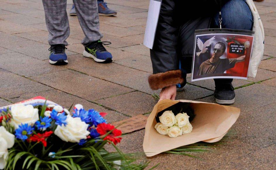 Her ses blomster og et billede til minde om den franske historielærer Samuel Paty, som blev slået ihjel i en forstad til Paris i oktober sidste år. Mordet har aktualiseret debatten om brugen af Muhammed-tegninger i undervisningen i flere lande. – Foto: Pascal Rossignol/Reuters/Ritzau Scanpix.