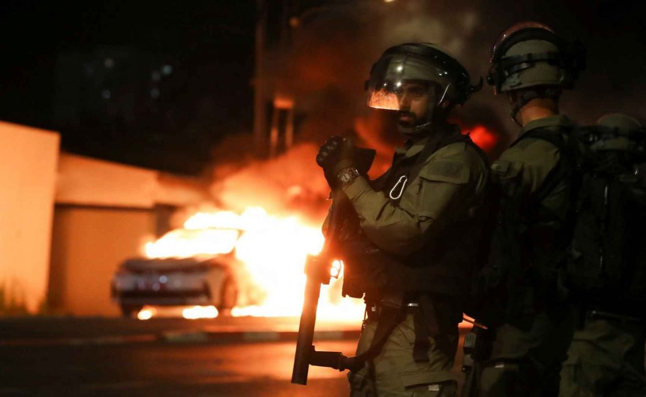 I den israelske by Lod er der erklæret undtagelsestilstand, og fra klokken 20 om aftenen til klokken fire om morgenen er der udgangsforbud. De israelske myndigheder har sendt grænsepolitiet, der under normale forhold er udstationeret i Østjerusalem og på Vestbredden, til byen for at skabe ro. Her ses medlemmer af den israelske sikkerhedsstyrke foran en brændende politibil i byen.