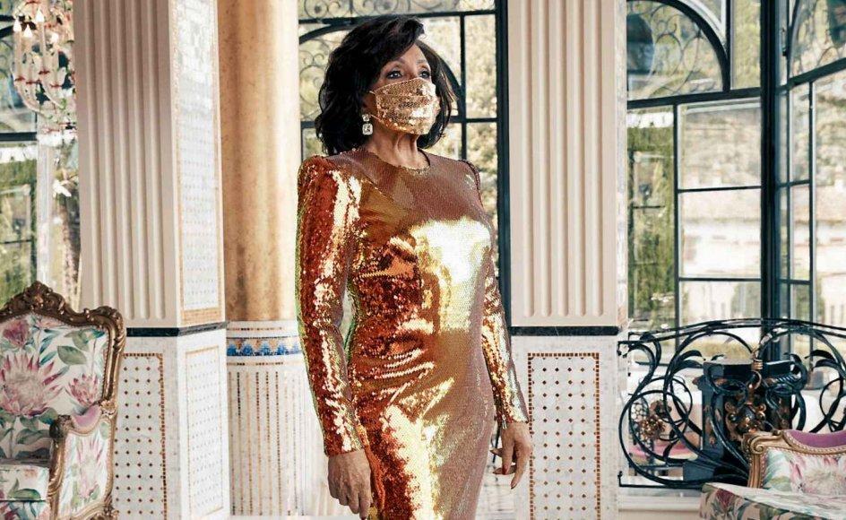 """Den 84-årige walisiske sangerinde Shirley Bassey, der er særligt kendt for titelsangene til tre klassiske """"James Bond""""-film, viser her, hvordan man gør en dyd ud af nødvendigheden med et mundbind, der matcher resten af tøjvalget, i dette tilfælde en guldkjole. – PR-foto: mensweararchive.com"""