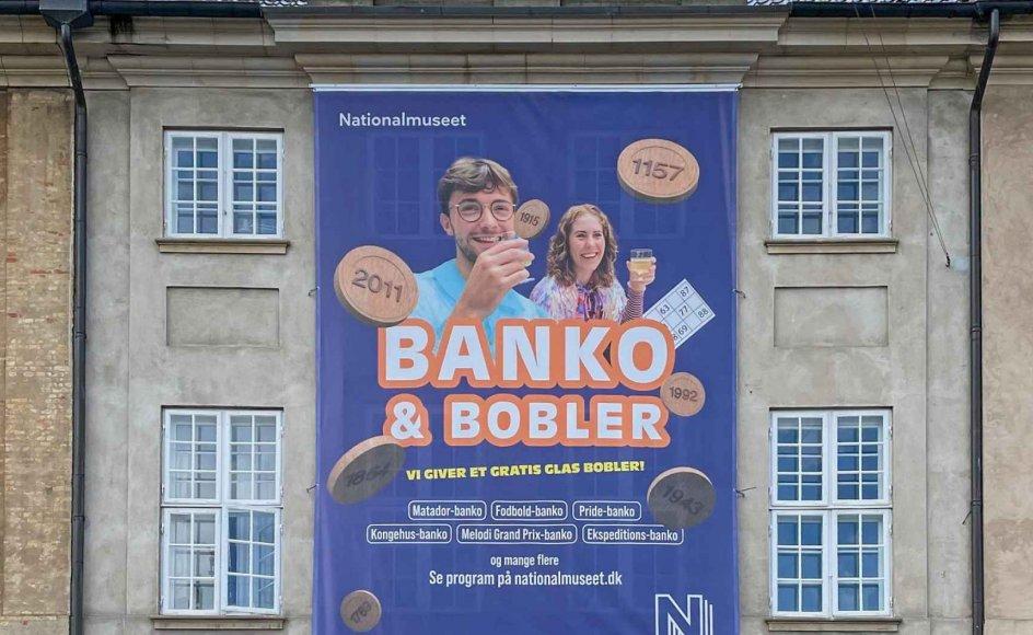 """Et stort banner på Nationalmuseet reklamerer for """"Banko & Bobler"""". Men det er stærkt tvivlsomt, om den type arrangementer vil ændre ved museets faldende besøgstal, skriver rådmand Nikolaj Bøgh (K)."""
