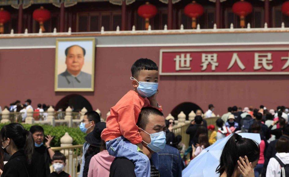 En mand med et barn med mundbind ved Tiananmen Porten nær et portræt af Mao Zedong. Kina lemper nu sin lovgivning for familieplanlægning, så det bliver tilladt at have tre børn per par. Det skriver statslige medier i Beijing.
