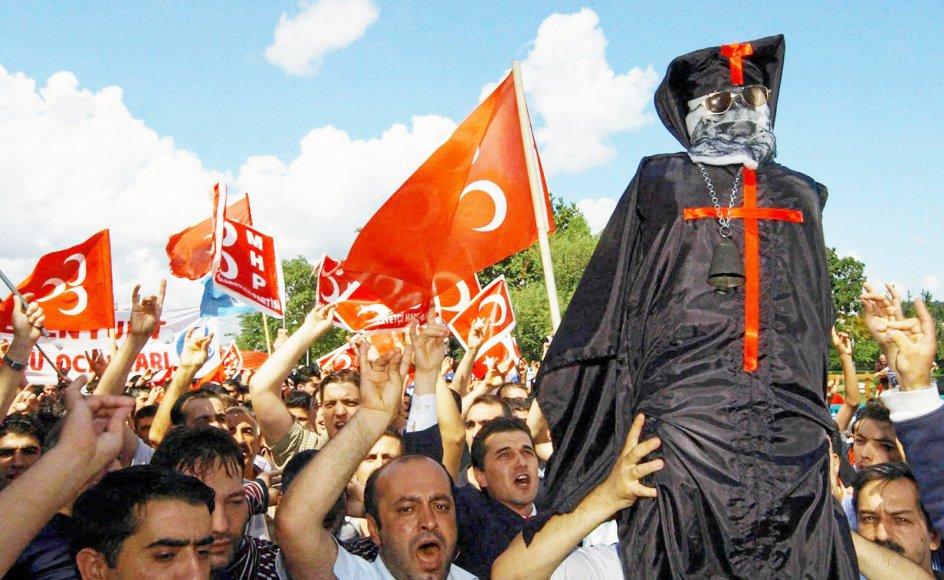Det er ikke alle tyrkere, der er lige begejstrede for landets kristne. Her holder nationalistiske demonstranter en dukke, der skal forestille den græske patriark Bartholomæus I, som senere blev brændt. Scenen er fra en protest mod krav om at genåbne præsteseminariet på Halki.