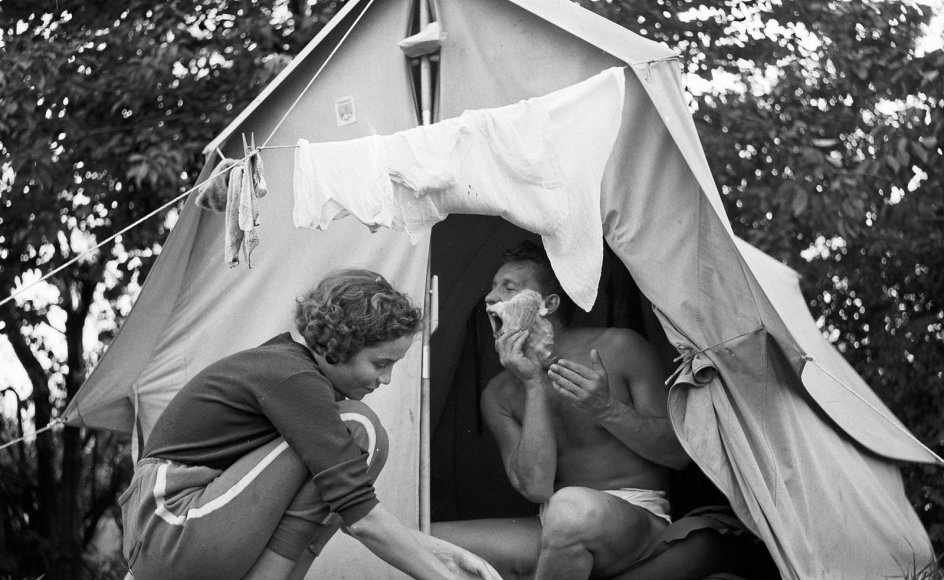 En julidag i 1958 klarer en kvinde opvasken i teltåbningen, mens hendes mand barberer sig. Den primitive ferieform har udviklet sig en del siden.
