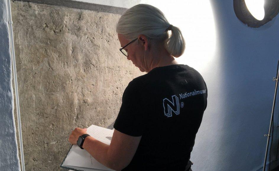 Seniorforsker Lisbeth Imer aftegner indskrifter på den oprindelige vægflade i koret i Tjæreby Kirke. Det vinklede lys får indskrifterne til at træde tydeligt frem.