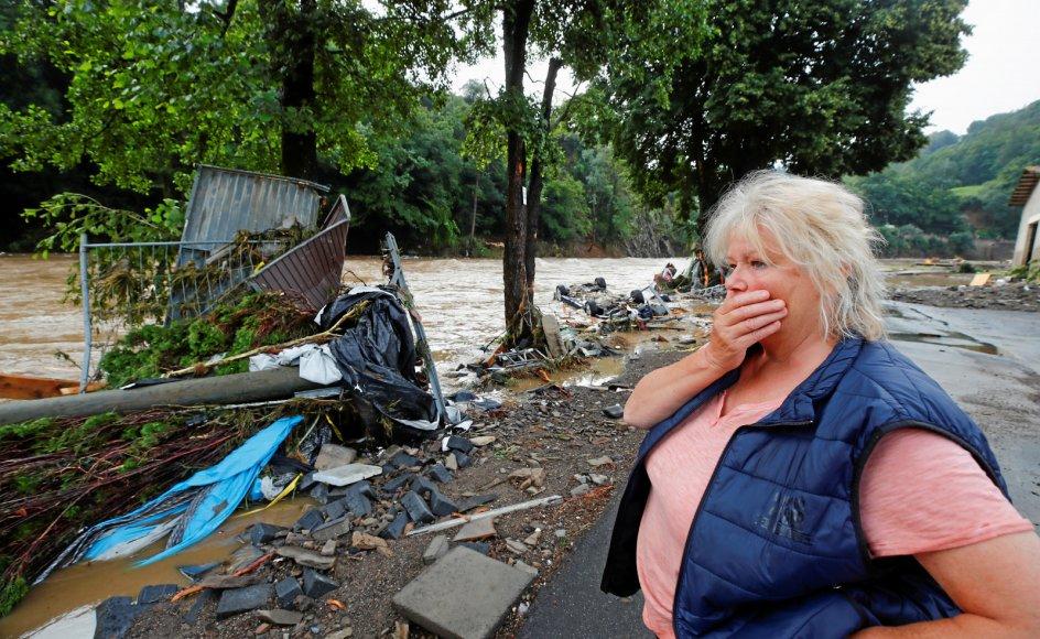 En kvinde ser på mens vragrester flyder forbi i floden Ahr i Schuld i Tyskland. Mange har mistet hus og hjem, og flere er stadig savnet.