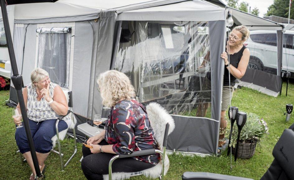 54-årige Randi Larsen (til højre) har inviteret nabocampisterne 56-årige Ulla Pedersen (til venstre) og 56-årige Dorthe Find (i midten) forbi til et koldt glas i skyggen. De tre kvinder og deres mænd er med årene blevet en sammentømret gruppe, som tilbringer store dele af sommeren sammen og holder kontakten, når sæsonen er slut.