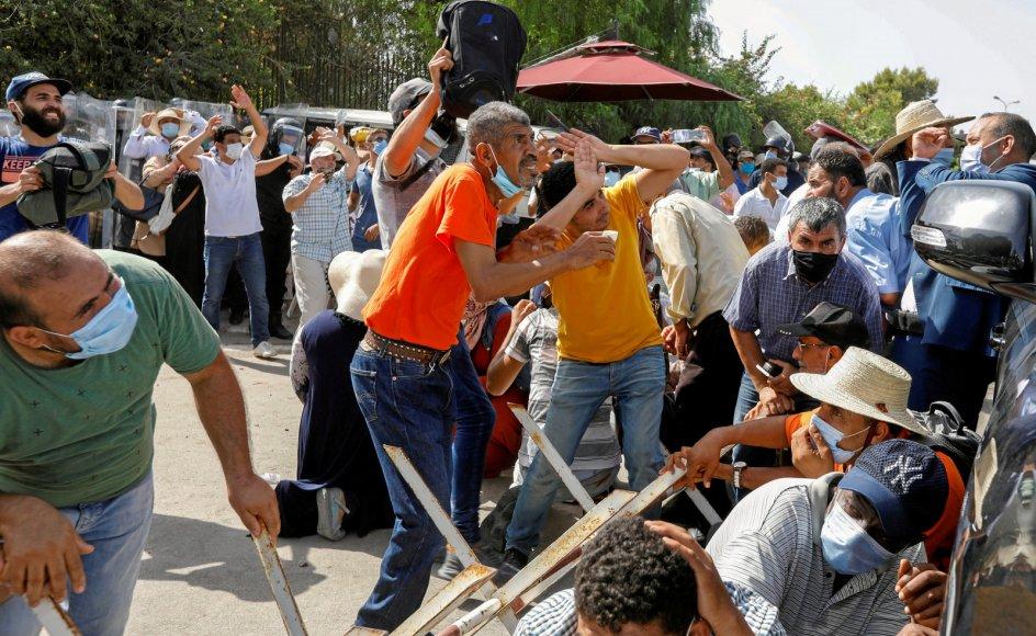 Vrede tunesere kastede i går sten mod tilhængere af det islamistiske regeringsparti Ennahda uden for parlamentet i Tunis.