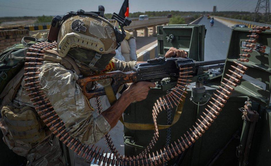 En afghansk soldat holder vagt fra et militærkøretøj uden for et af FN's kontorer i Herat-provinsen lørdag. Herat er en af de provinser, hvor der i disse dage er hårde kampe mellem hæren og Taliban.