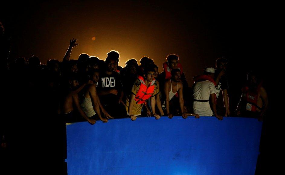 Migranter om bord på den overfyldte træbåd, der var begyndt at tage vand ind, venter på hjælp fra redningsskibene. Migranterne var primært mænd fra Marokko, Bangladesh, Egypten og Syrien.