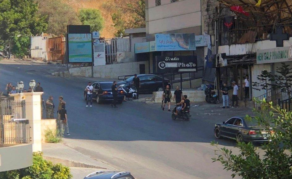 Soldater og andre står på den gade i byen Khaldeh i Libanon, hvor mindst tre mennesker lørdag er blevet dræbt af skud mod deltagere ved et Hizbollah-medlems begravelse.