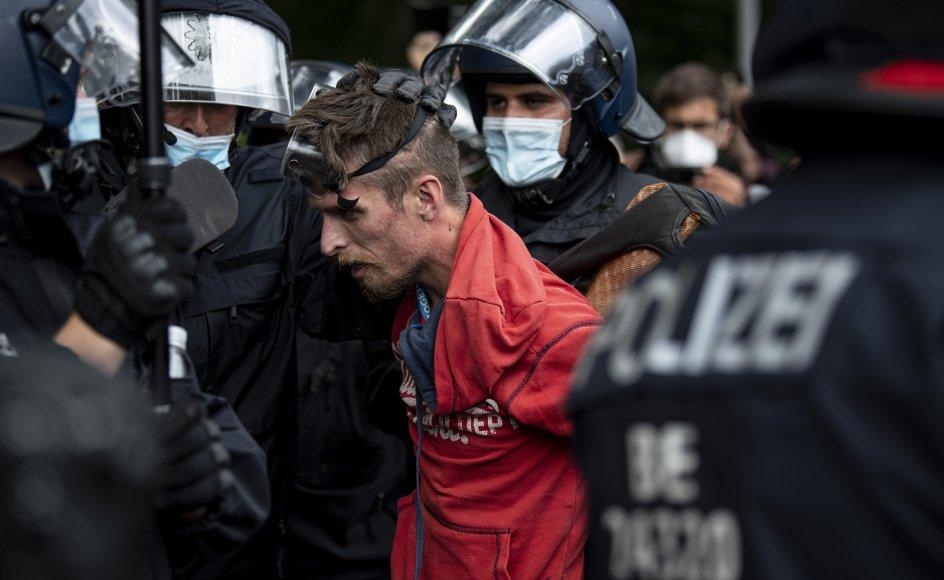 Politi anholder en demonstrant under søndagens coronaprotest i Berlin. I alt er over 600 anholdt.
