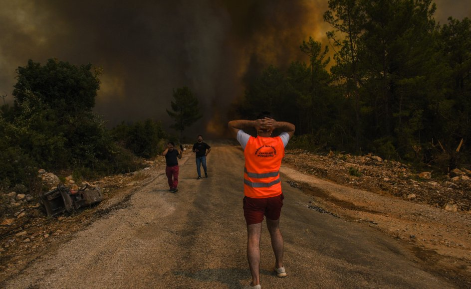 Folk på vild flugt fra en skovbrand nær den tyrkiske landsby Sirtkoy øst for Antalya ved Tyrkiets sydlige middelhavskyst. To personer i området mistede søndag livet i branden.