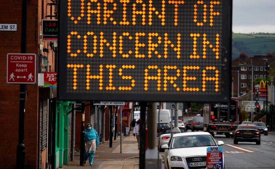 En kvinde går forbi et skilt på gaden i byen Bolton, der advarer om smitte i hendes område.