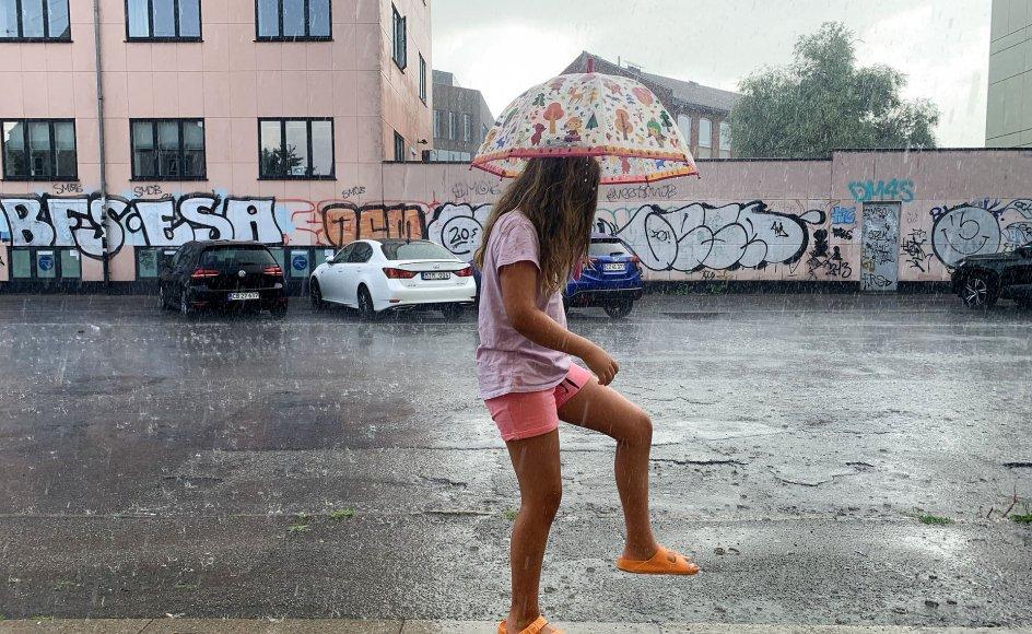 """""""Man søger jo ofte det hurtige svar på, hvornår der kommer regn. Hvis det ikke ligner det i vejrudsigten, bliver man skuffet, når det så står ned i stænger to timer efter. Så det er en enormt svær kommunikationsopgave,"""" siger meteorolog Herdis Damberg. På billedet ses en pige på gaden i København, som har helgarderet sig med både shorts og paraply."""