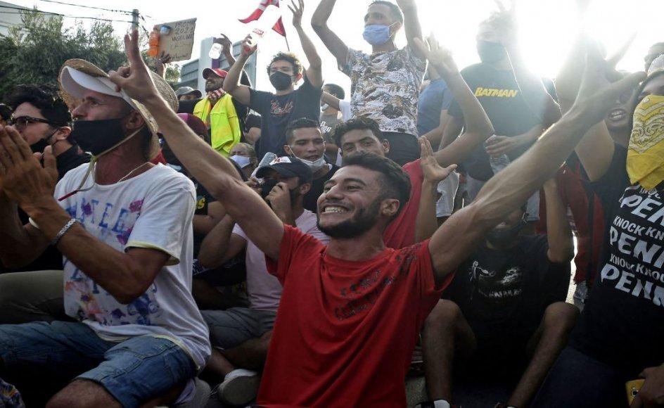 Tunesere jubler foran den militærbeskyttede parlamentsbygning, efter at Tunesiens præsident Kais Saied i søndags fyrede premierministeren og opløste parlamentet. Nu står det unge demokrati i en konstitutionel krise.