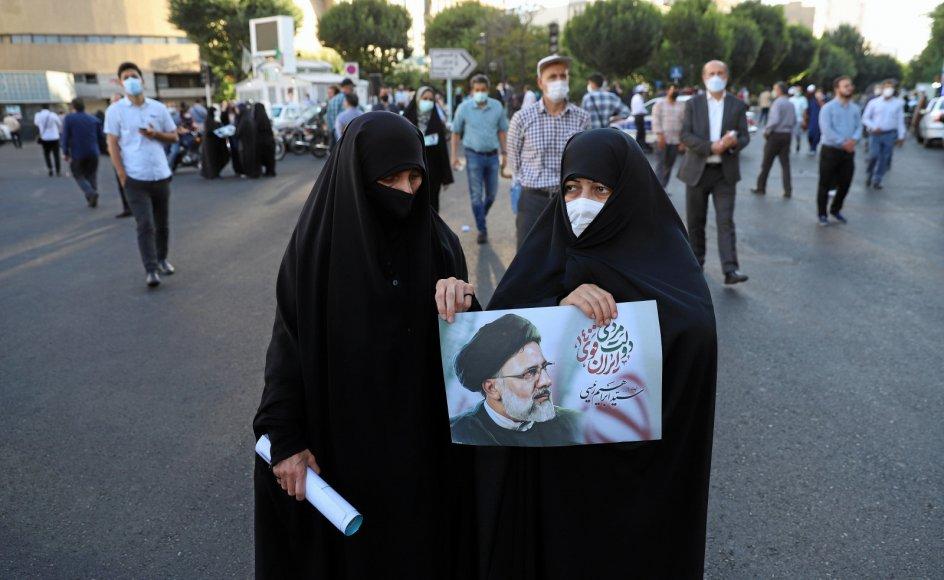 To iranske kvinder holder plakat af deres favoritkandidat Ebrahim Raisi forud for dagens præsidentvalg. På grund af stor intern utilfredshed med regimet ventes valgdeltagelsen ikke at komme over 40 procent af de 59 millioner iranere med stemmeret.
