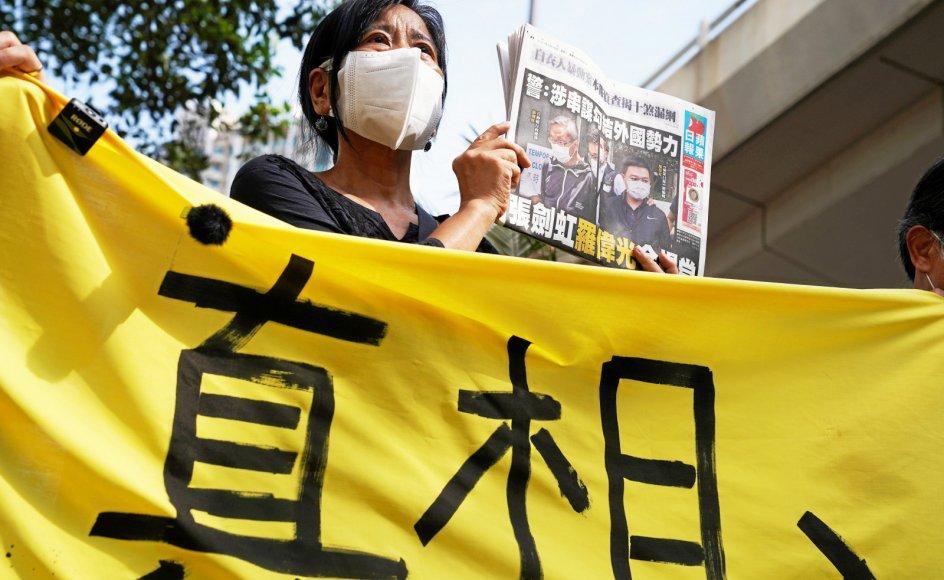 De seneste dage er pro-demokratiske aktivister igen gået på gaden i Hongkong, denne gang for at støtte den systemkritiske avis Apple Daily. Her står en demonstrant foran byens distriksdomstol med en udgave af avisen med billedet på forsiden, hvor to af avisens medieledere bliver ført bort i håndjern.