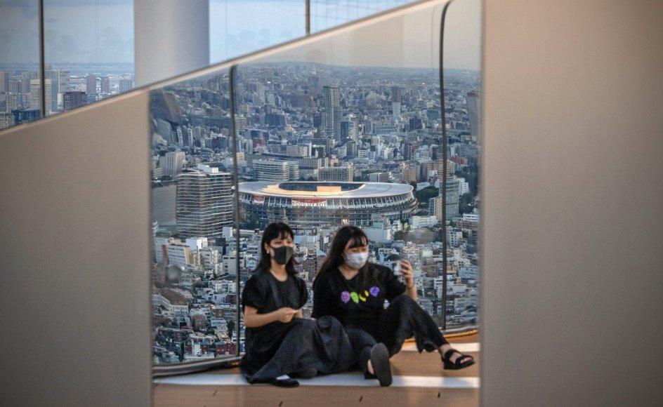 To yngre kvinder tager en selfie i et højhus med det olympiske stadion i Tokyo i baggrunden. OL foregår nu uden tilskuere som følge af stigende coronasmitte i den japanske hovedstad, og den langvarige pandemi har især ramt mange kvinders mentale helbred.